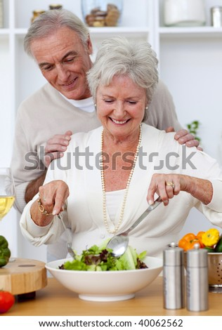 Happy senior couple eeating a salad in the kitchen and drinkng wine - stock photo