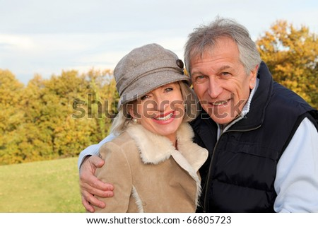 Happy senior couple embracing each other in countryside - stock photo