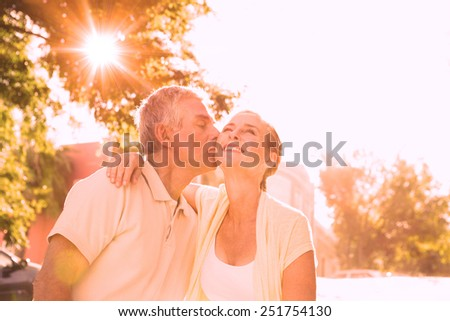 Happy senior couple embracing in the city on a sunny day - stock photo