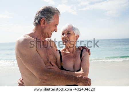 Happy senior couple embracing on the beach on a sunny day - stock photo