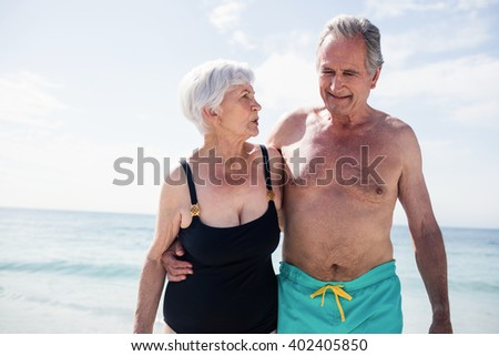 Happy senior couple embracing while walking on beach on a sunny day - stock photo