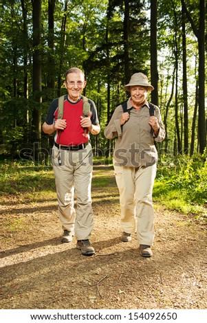 Happy senior couple enjoy hiking in woods. - stock photo
