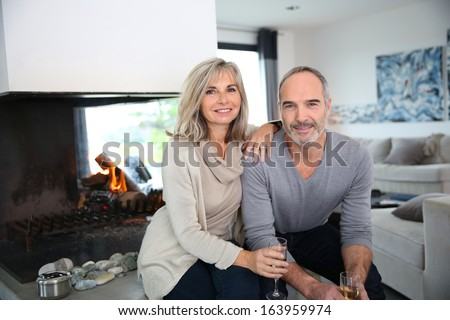 Happy senior couple enjoying glass of champagne - stock photo