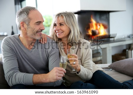 Happy senior couple enjoying glass of champagne - stock photo