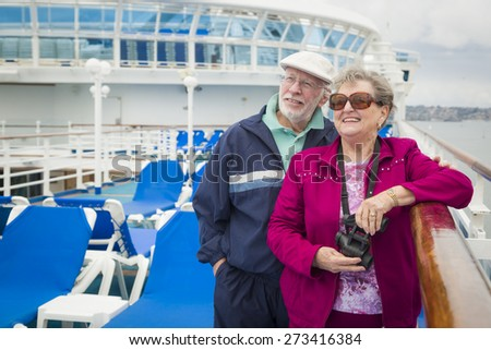 Happy Senior Couple Enjoying The View From Deck of a Luxury Passenger Cruise Ship. - stock photo