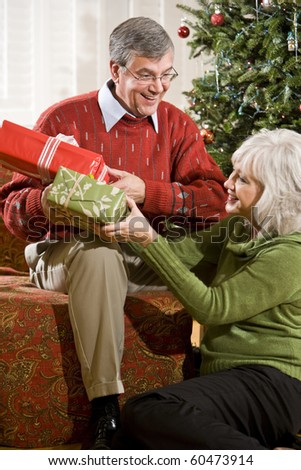 Happy senior couple exchanging Christmas gifts at home by tree