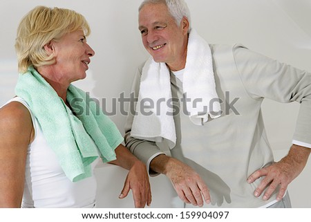 Happy senior couple exercising in fitness center  towel on the shoulder - with a look of complicity