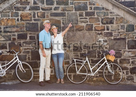 Happy senior couple going for a bike ride in the city on a sunny day - stock photo