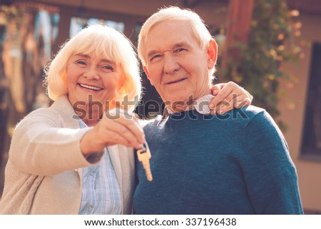 Happy senior couple. Happy senior couple bonding to each other and smiling while woman holding keys in her hand