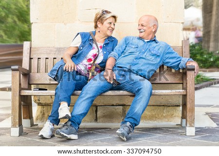 Happy senior couple having fun on a bench - Concept of active playful elderly during retirement - Everyday lifestyle in autumn sunny afternoon - Soft vintage filtered look with slightly blurred edges - stock photo