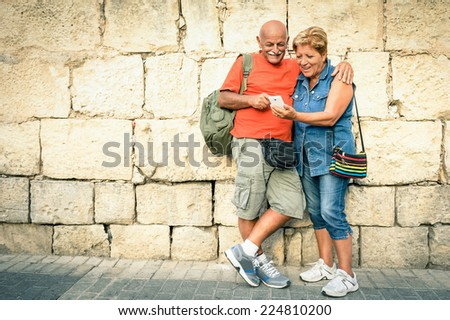 Happy senior couple having fun with a modern smartphone - Concept of active elderly and interaction with new technologies - Travel lifestyle without age limitation - stock photo
