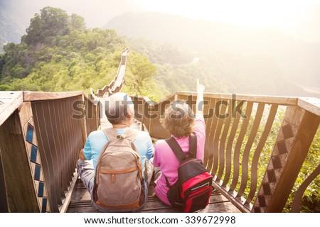happy   senior couple hiking on the mountain  - stock photo