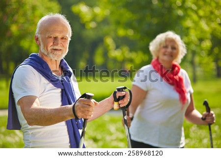 Happy senior couple hiking together in summer in nature - stock photo