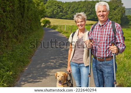 Happy senior couple hiking with their dog in nature in summer - stock photo
