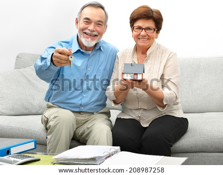 Happy senior couple holding a small house and keys in hands - stock photo