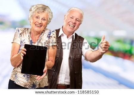 Happy Senior Couple Holding Digital Tablet, Indoor - stock photo