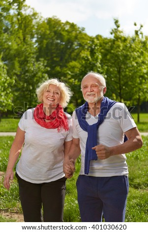 Happy Senior couple holding hands in a green park - stock photo