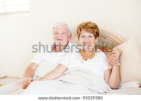happy senior couple holding hands in bed - stock photo