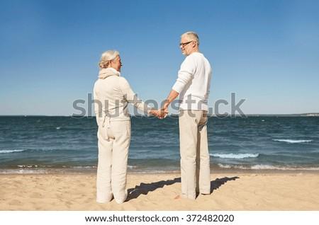 happy senior couple holding hands summer beach - stock photo
