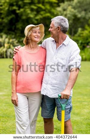 Happy senior couple holding rake while standing in yard - stock photo
