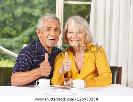 Happy senior couple holding thumbs up at coffee table - stock photo