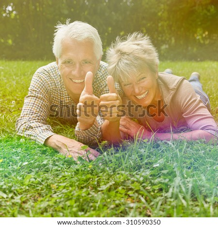 Happy senior couple holding thumbs up to congratulate - stock photo