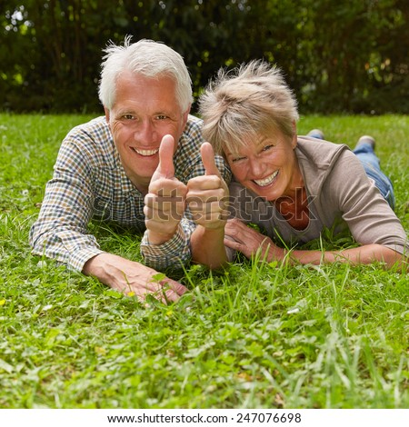 Happy senior couple holding two thumbs up for congratulation - stock photo