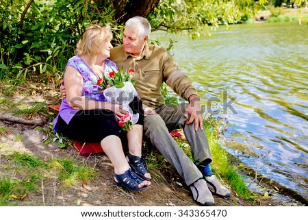 Happy senior couple hugging and talking near the pond