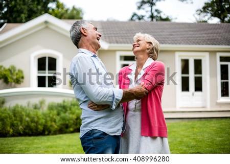 Happy senior couple hugging outside house in yard - stock photo