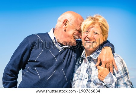 Happy senior couple in love during retirement - Joyful elderly lifestyle with man whispering and smiling with her wife - stock photo