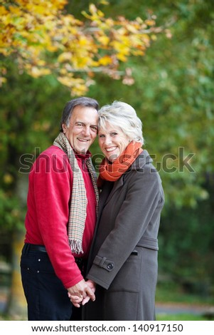 Happy senior couple in love holding hands outdoor in a summer day - stock photo