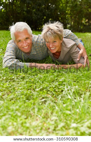 Happy senior couple in love laying on a meadow in summer - stock photo