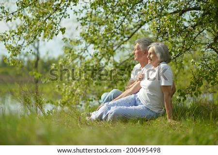 Happy senior couple in summer near lake - stock photo