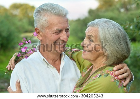Happy senior couple  in summer near lake