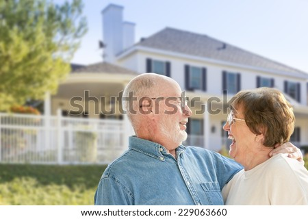 Happy Senior Couple in the Front Yard of Their House. - stock photo