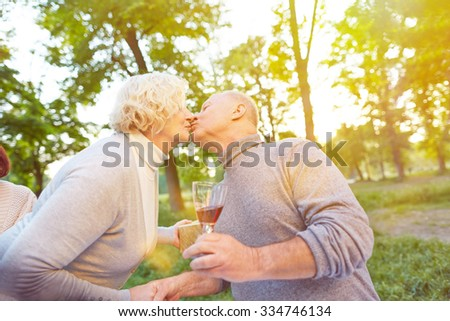Happy senior couple kissing at birthday party with gift and wine