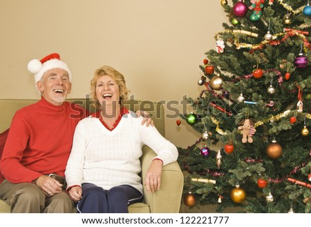 Happy senior couple laughing beside Christmas tree