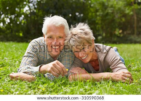 Happy senior couple laying together in grass in a meadow - stock photo