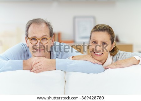 happy senior couple leaning on the white sofa looking at the camera with a smile