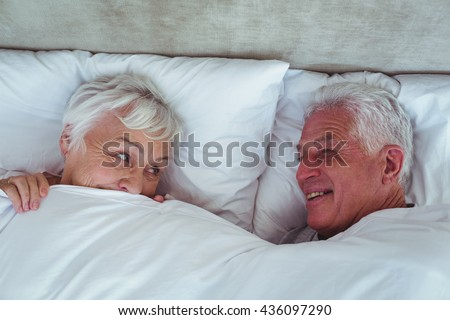 Happy senior couple looking at each other while lying on bed in room - stock photo