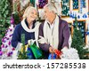 Happy senior couple looking at each other while shopping for decorations in Christmas store - stock photo