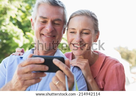 Happy senior couple looking at smartphone on a sunny day - stock photo