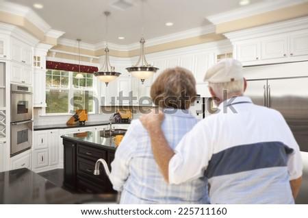Happy Senior Couple Looking Over Beautiful Custom Kitchen Design. - stock photo