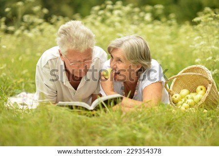 Happy senior couple lying in summer field