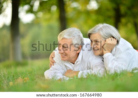 Happy senior couple lying in summer park - stock photo