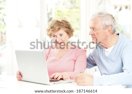 Happy senior couple planning for retirement at home.  - stock photo