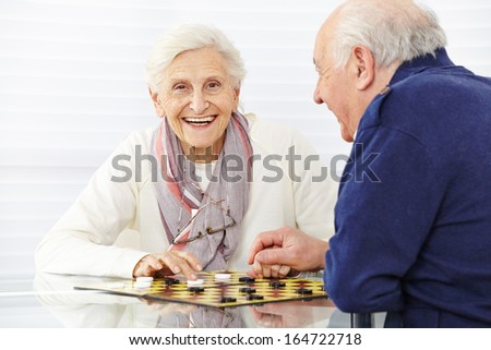 Happy senior couple playing checkers in a retirement home - stock photo