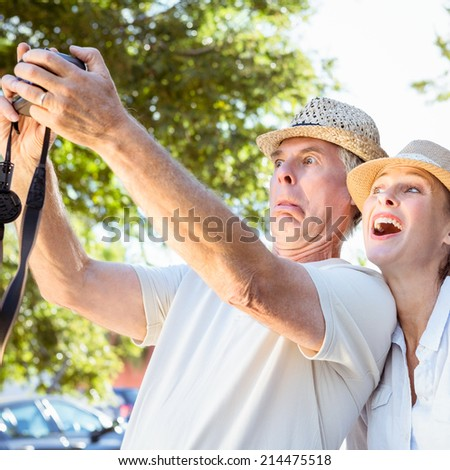 Happy senior couple posing for a selfie on a sunny day - stock photo