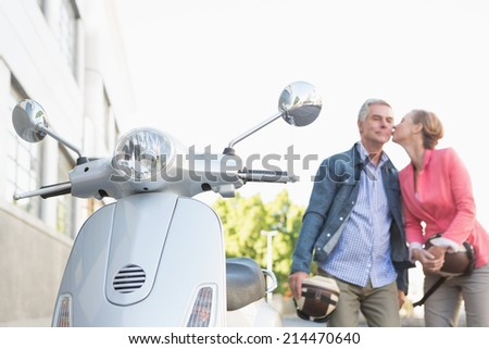 Happy senior couple posing with their moped on a sunny day - stock photo