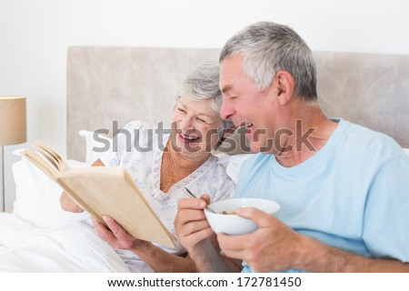 Happy senior couple reading book in bed at home - stock photo